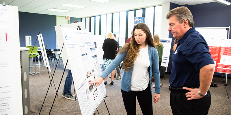 Female Student Presenting Research poster